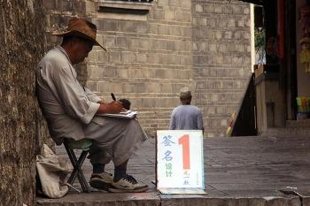 칭옌고진 중심거리에 앉아 사인 만들어주는 사람이 있다
