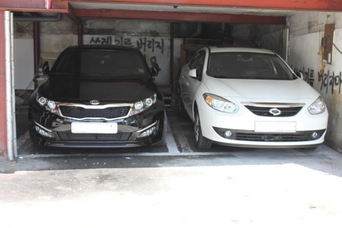 주차장에 주차된 KIA K5와 다른 자동차