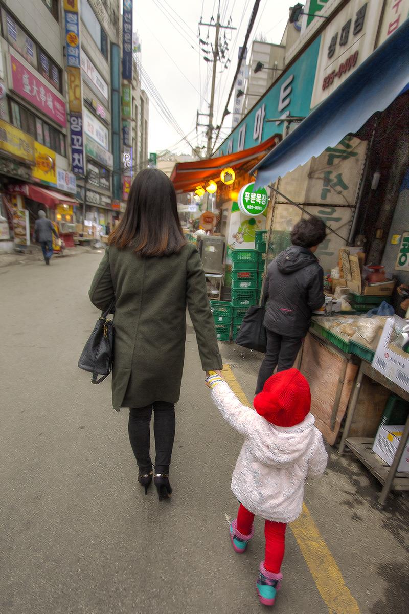 성큼성큼 걸어가는 엄마손을 잡고 아장아장 짧은 보폭으로 걸어가는 아이가 담겨진 사진.