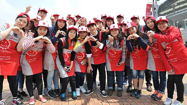 BC카드 모델인 정용화씨와 봉사단원들이 기념촬영을 하고 있다.