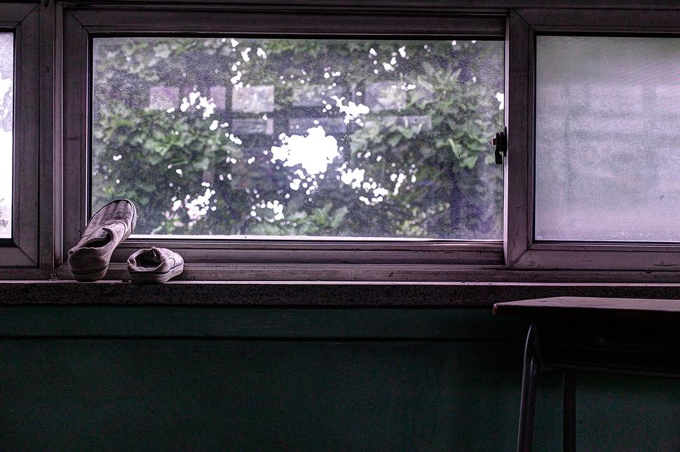 빛바랜 창문에 오래된 실내화가 한켤레놓여있다.