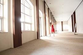 빨간 드레스를 입은 소녀가 복도에서 뽀샤시한 햇살을 받으며 거울에 포즈를 잡는 발레 동작