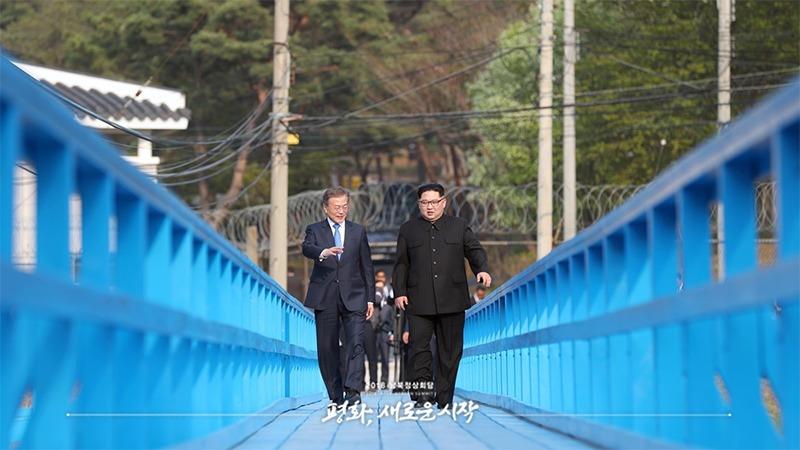 사진: 문재인 대통령과 김정은 위원장이 다리를 건너며 대화를 나누고 있다.